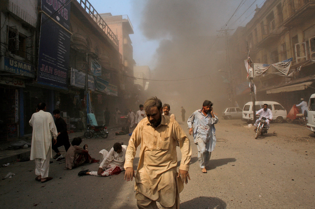 . Pakistani men rush away from the site of a blast shortly after a car explosion in Peshawar, Pakistan, Sunday, Sept. 29, 2013.  (AP Photo/Mohammad Sajjad)