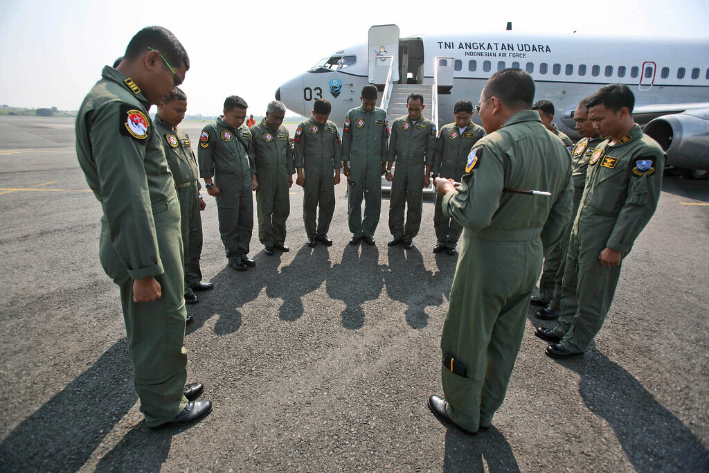 """. Indonesian Air Force crewmen of a Boeing 737 \""""Surveiller\"""" maritime patrol aircraft of the 5th Air Squadron \""""Black Mermaids\"""" pray prior to a search operation for the missing Malaysia Airlines Boeing 777 that will be conducted the Strait of Malacca, at Suwondo air base in Medan, North Sumatra, Indonesia, Wednesday, March 12, 2014.  (AP Photo/Binsar Bakkara)"""