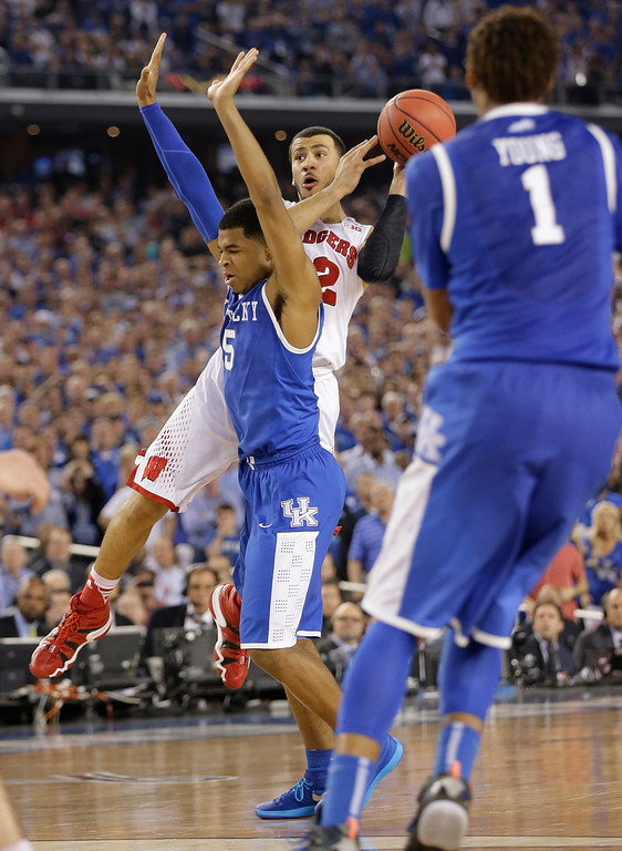 . Wisconsin guard Traevon Jackson (12) is fouled by Kentucky guard Andrew Harrison (5) during the final seconds of their NCAA Final Four tournament college basketball semifinal game Saturday, April 5, 2014, in Arlington, Texas. (AP Photo/Eric Gay)