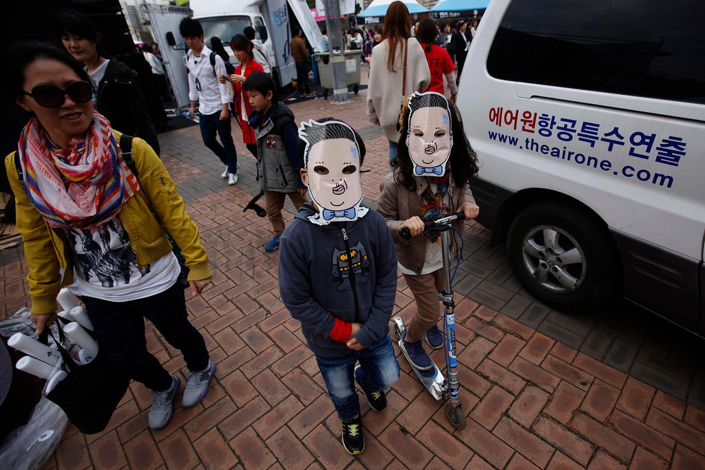 """. Children wearing a mask of South Korean rapper Psy play at the Seoul World Cup stadium, the venue for Psy\'s concert \""""happening\"""" in Seoul April 13, 2013. Psy will perform \""""Gentleman\"""" in public for the first time on Saturday at a concert at Seoul\'s World Cup stadium but he has been coy about what dance to expect this time, except to hint that it is based on traditional Korean moves. Psy released his new single on Thursday hoping to repeat the success of \""""Gangnam Style\"""" that made him the biggest star to emerge from the growing K-pop music scene.   REUTERS/Kim Hong-Ji"""