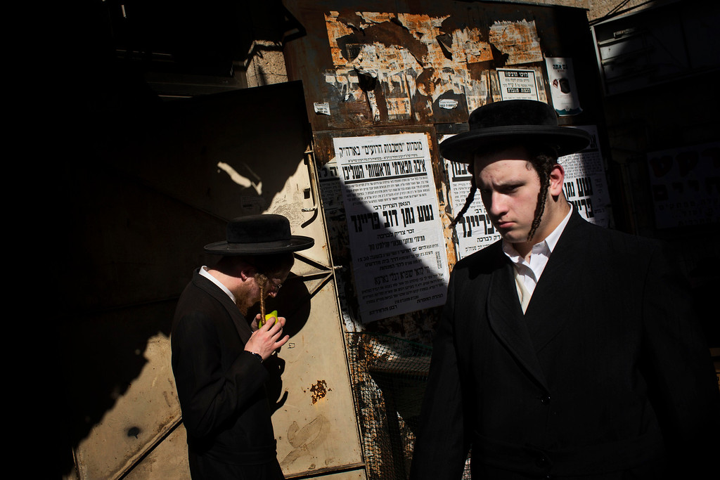 . An ultra-Orthodox Jewish man checks an etrog, a lemon-like citrus fruit, for blemishes to determine if is ritually acceptable, before buying it as one of the four items used as a symbol on the Jewish holiday of Sukkot in Jerusalem\'s Mea Shearim neighborhood, Tuesday, Sept. 17, 2013. The holiday commemorates the Israelites 40 years of wandering in the desert and a decorated hut is erected outside religious households as a sign of temporary shelter. (AP Photo/Bernat Armangue)