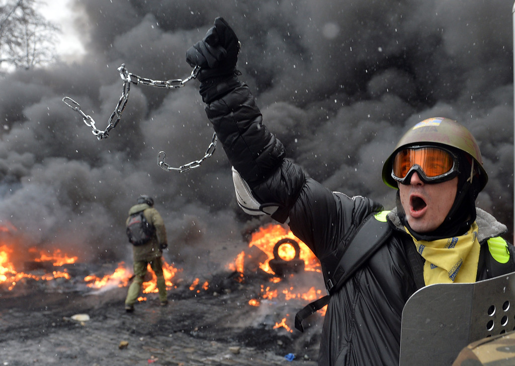 . A demonstrator holds up a chain and a riot police shield as protestors clash with police in the center of Kiev on January 22, 2014.  AFP PHOTO / SERGEI SUPINSKY/AFP/Getty Images