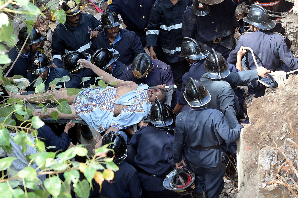 . Firefighters carry out a victim from the rubble at the site of a building collapse in Mumbai on September 27, 2013. AFP PHOTO/Indranil MUKHERJEE/AFP/Getty Images
