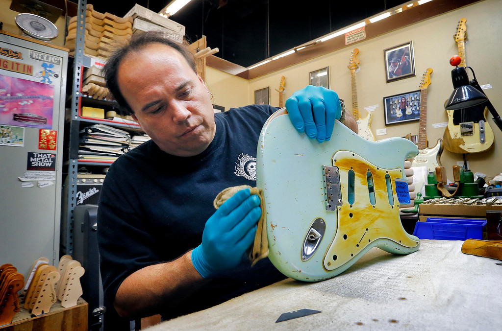 . Fender Custom Shop Master Builder John Cruz works on a heavily-used Fender Stratocaster body at the Fender factory in Corona, Calif. on Tuesday, Oct. 15, 2013. Leo Fender developed the instrument in a small workshop in Fullerton, Calif. six decades ago. (AP Photo/Matt York)