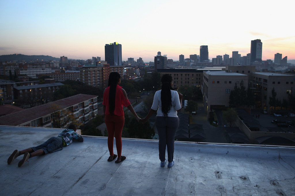 . PRETORIA, SOUTH AFRICA - JUNE 27:  Residents of a nearby tower block stand on the roof looking over the Heart Hospital where Mandela is being treated for a lung infection June 27, 2013 in Pretoria, South Africa. Family members and President Jacob Zuma visited Mandela during his 20th day in the hospital.  (Photo by Dan Kitwood/Getty Images)