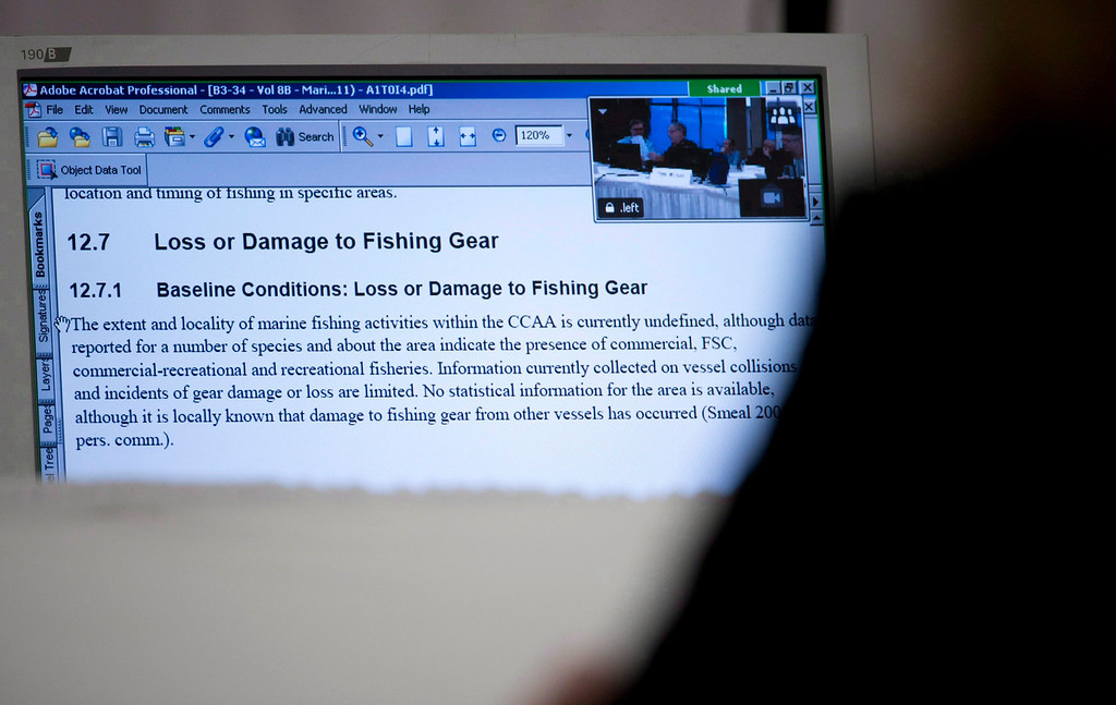 . A panel member is seen looking at a screen during a session regarding loss and damage to fishing gear during the Northern Gateway hearings in Prince Rupert, B.C. on Dec. 11, 2012.   (AP Photo/The Canadian Press, Jonathan Hayward)