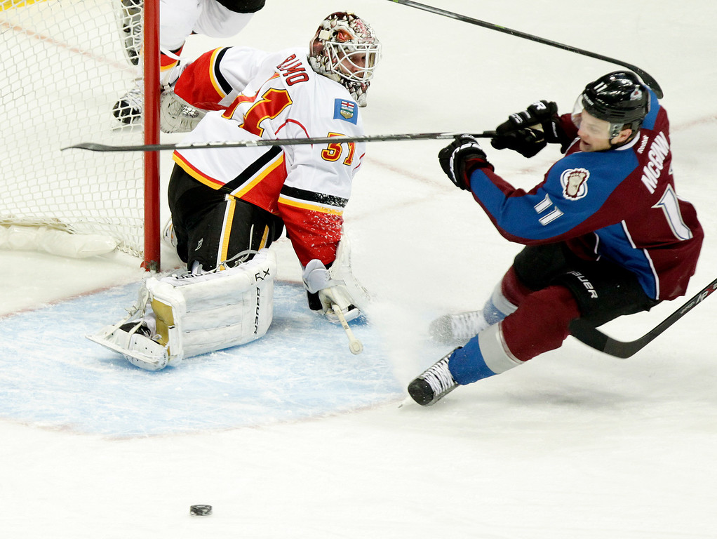 . Calgary Flames goalie Karri Ramo (31), of Finland, watches as Colorado Avalanches\' Jamie McGinn (11) misses the puck in front of the net during the first period of an NHL hockey game on Friday, Nov. 8, 2013, in Denver. (AP Photo/Barry Gutierrez)