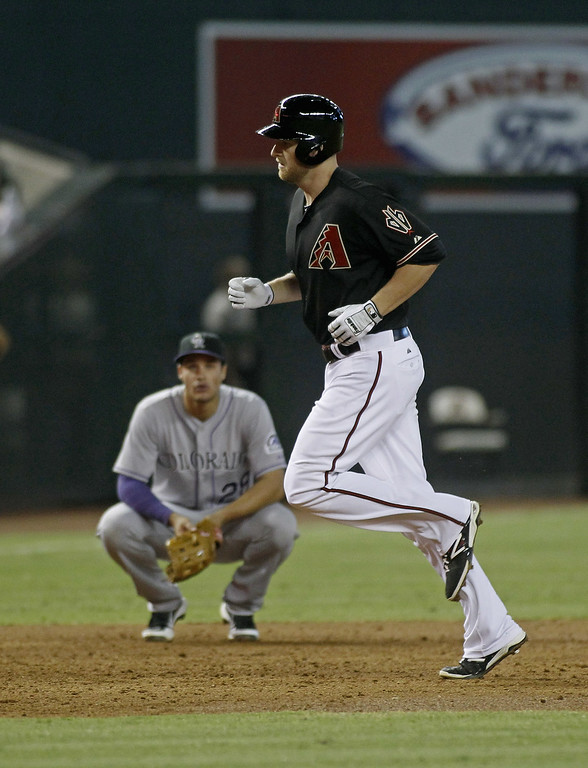 . Mark Trumbo #15 of the Arizona Diamondbacks (R) runs past third baseman Nolan Arenado #28 of the Colorado Rockies after his three-run home run during the third inning of a MLB game at Chase Field on August 9, 2014 in Phoenix, Arizona.  (Photo by Ralph Freso/Getty Images)