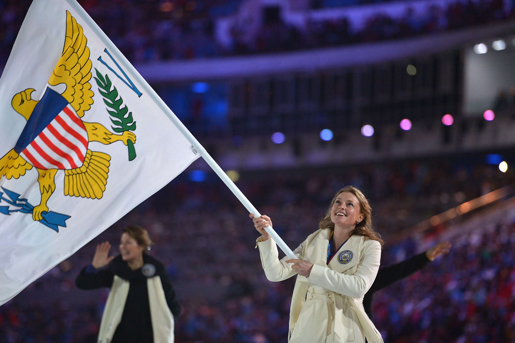. Virgin Islands\' flag bearer, alpine skier Jasmine Campbell , leads her national delegation during the Opening Ceremony of the 2014 Sochi Winter Olympics at the Fisht Olympic Stadium on February 7, 2014 in Sochi. AFP PHOTO / ALBERTO PIZZOLI/AFP/Getty Images