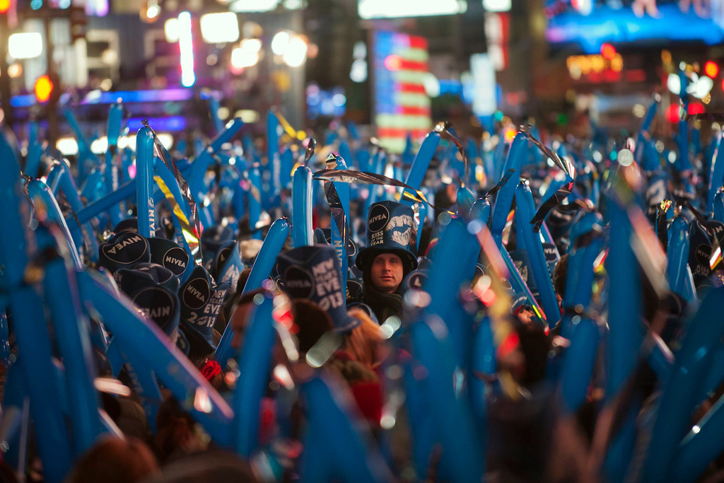 . Revelers stand in Times Square during New Year\'s Eve celebrations in New York December 31, 2012. REUTERS/Keith Bedford