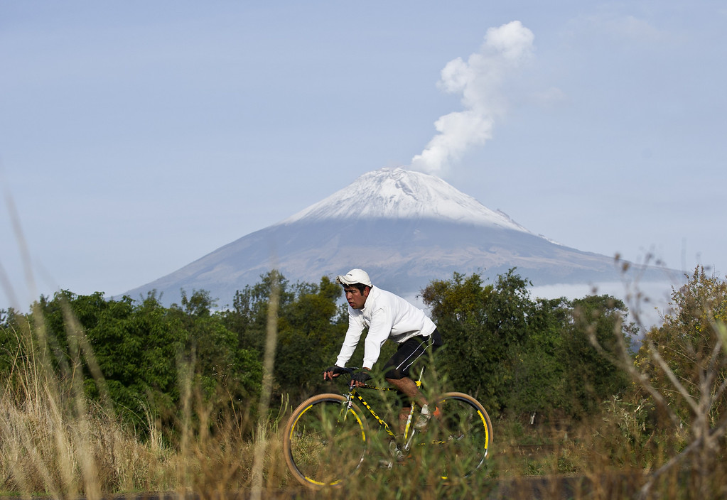". Backdropped by Popocatepetl Volcano, Mexico\'s second highest peak just 55 km southeast of Mexico City, a man rides his bicycle in San Nicolas de los Ranchos, in the state of Puebla, on May 14, 2013. The National Disaster Prevention Centre (CENAPRED) raised the alert level on Sunday to ""yellow phase three\"" as the Popocatepetl continues to spew ash and smoke. Ronaldo Schemidt/AFP/Getty Images"