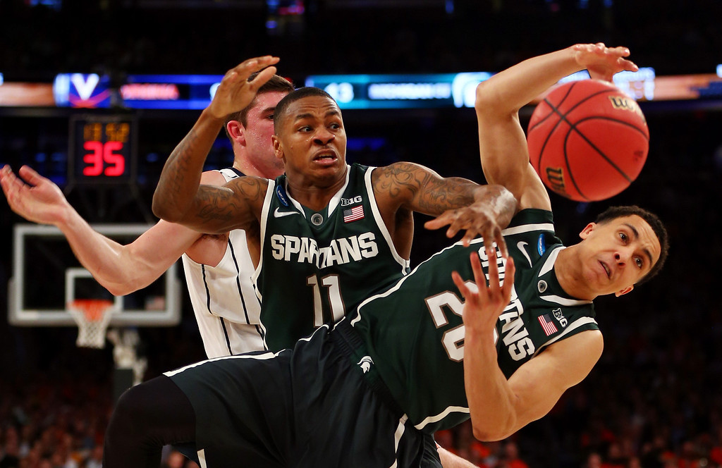 . Keith Appling #11 and Travis Trice #20 of the Michigan State Spartans fights for the loose ball against Mike Tobey #10 of the Virginia Cavaliers during the regional semifinal of the 2014 NCAA Men\'s Basketball Tournament at Madison Square Garden on March 28, 2014 in New York City.  (Photo by Elsa/Getty Images)