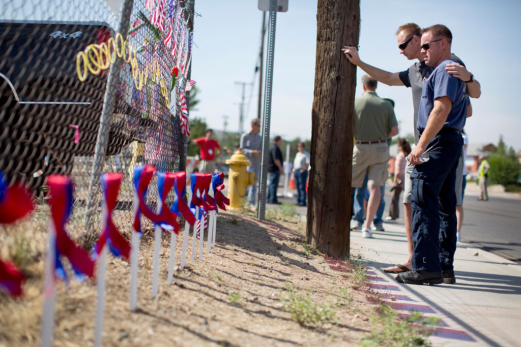 . Two unidentified firefighters stand at a memorial outside the Granite Mountain Interagency Hotshot Crew fire station, Tuesday, July 2, 2013 in Prescott, Ariz.  (AP Photo/Julie Jacobson)