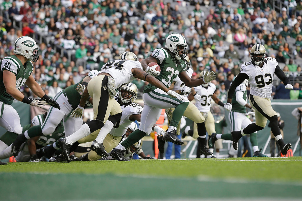 . New York Jets\' Chris Ivory (33) rushes past New Orleans Saints\' Corey White (24) during the first half of an NFL football game Sunday, Nov. 3, 2013, in East Rutherford, N.J.  (AP Photo/Mel Evans)