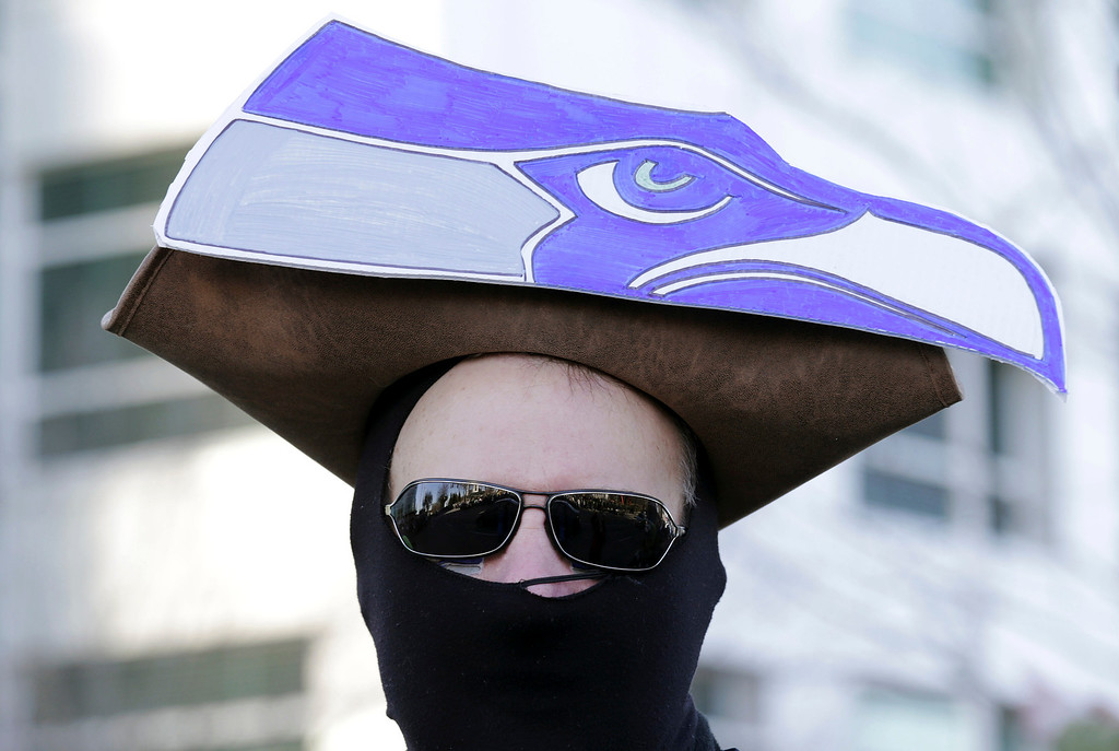 . A Seattle Seahawks fan waits in the cold for the start of the Super Bowl champions parade to begin Wednesday, Feb. 5, 2014, in Seattle.(AP Photo/John Froschauer)