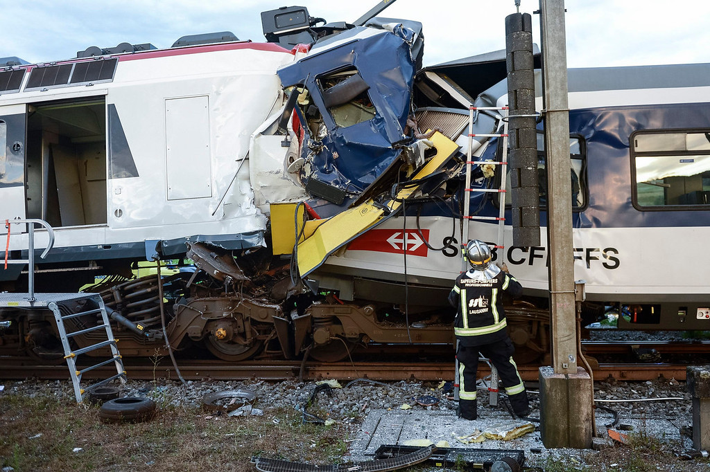 . A fireman works at the site where two passenger trains collided head-on in Granges-pres-Marnand, western Switzerland, Monday, July 29, 2013. Police say at least 44 people were injured, four of them seriously. (AP Photo/Keystone, Laurent Gillieron)