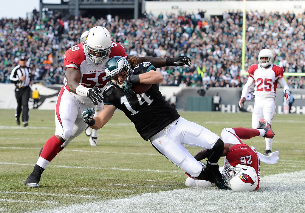 . Riley Cooper #14 of the Philadelphia Eagles is tackled by Rashad Johnson #26 of the Arizona Cardinals and Marcus Benard #59 during the second quarter at Lincoln Financial Field on December 1, 2013 in Philadelphia, Pennsylvania.  (Photo by Maddie Meyer/Getty Images)