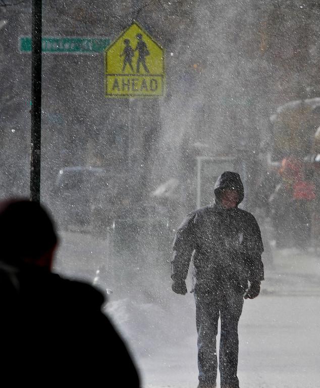 . A pedestrian is caught in a sudden dusting of wind-blown fallen snow on Wednesday Jan. 22, 2014 in New York. (AP Photo/Bebeto Matthews)