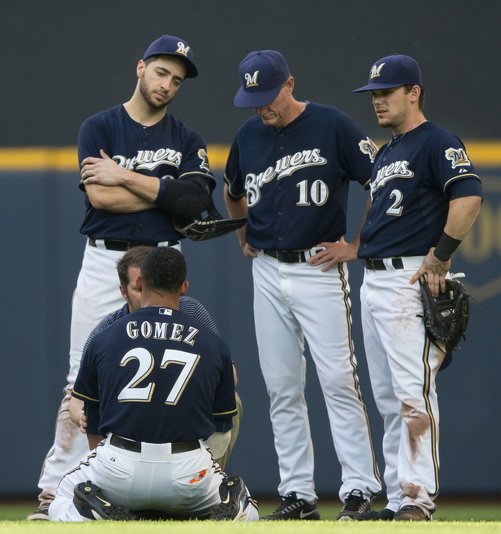 . Carlos Gomez of the Milwaukee Brewers is treated by a member of the training staff after colliding with Ryan Braun in the outfield against the Colorado Rockies during the seventh inning of a baseball game Saturday, June 28, 2014, in Milwaukee. Looking on are teammates Ryan Braun, Scooter Gennett and manager Ron Roenicke.  (AP Photo/Tom Lynn)