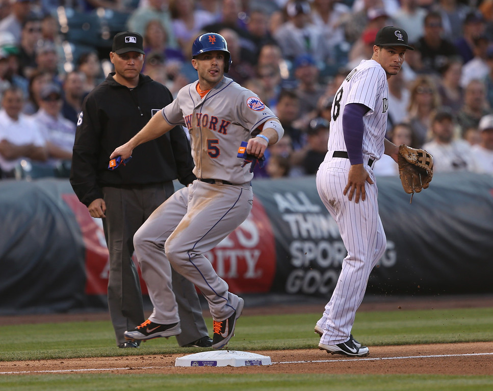 . New York Mets\' David Wright (5) reaches third base from first on an errant pickoff throw as Colorado Rockies third baseman Nolan Arenado, right, looks on with third base umpire Mark Carlson, left, watching in the fourth inning of a baseball game in Denver, Saturday, May 3, 2014. (AP Photo/David Zalubowski)