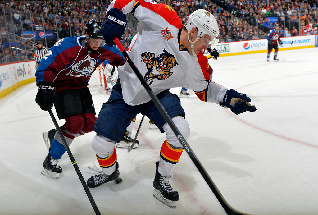 . Florida Panthers center Shawn Matthias (18) and Colorado Avalanche defenseman Nick Holden (2) go after the puck during the second period of an NHL hockey game on Saturday, Nov. 16, 2013, in Denver. (AP Photo/Jack Dempsey)