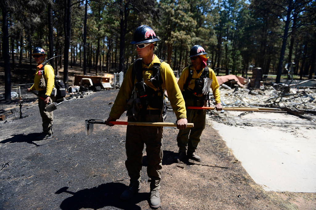 . BLACK FOREST, CO - JUNE 19: Long Canyon Wildland firefighters from left to right Chief Andrew Rose, Sean Sortland and Lynn Reynolds check for hotspots as the crew coal trails at a burned property on Pine Glen Drive. Only one home on the loop of Pine Glen Drive burned in the fire. (Photo by AAron Ontiveroz/The Denver Post)