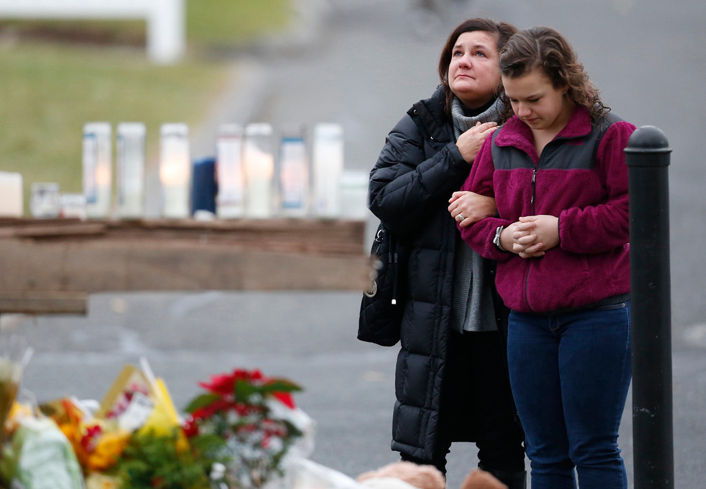 . People pay respects by a makeshift memorial outside of St. Rose of Lima Roman Catholic Church between Mass services, Sunday, Dec. 16, 2012, in Newtown, Conn. On Friday, a gunman allegedly killed his mother at their home and then opened fire inside the Sandy Hook Elementary School, killing 26 people, including 20 children. (AP Photo/Julio Cortez)