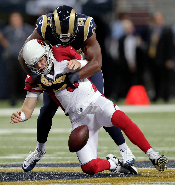 . Arizona Cardinals quarterback Carson Palmer, bottom, fumbles the ball as he is sacked for a 7-yard loss by St. Louis Rams defensive end Robert Quinn during the first quarter of an NFL football game on Sunday, Sept. 8, 2013, in St. Louis. The Cardinals recovered the fumble. (AP Photo/Tom Gannam)