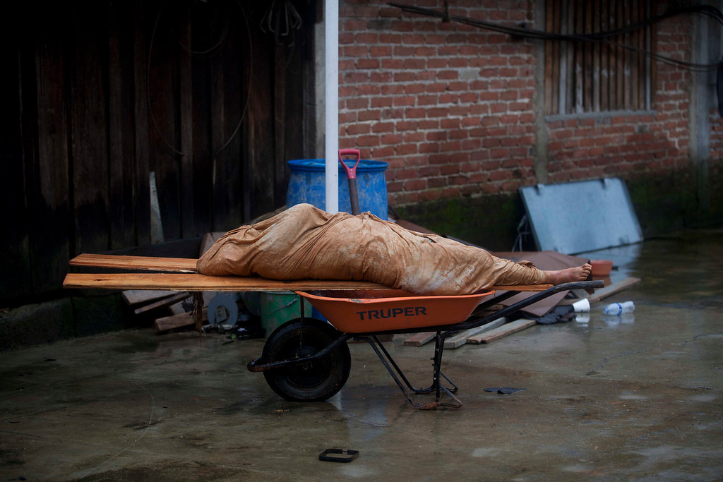 . In this Saturday, Sept. 21, 2013 photo, the body of a landslide victim, lies on two wooden slats atop a wheelbarrow in La Pintada, Mexico, where a landslide swept through the village center. Fourteen hours per body is how long rescue crews with shovels, hydraulic equipment, were averaging to recover victims of a massive landslide that took half the remote coffee-growing village of La Pintada, leaving 68 people missing. (AP Photo/Eduardo Verdugo)