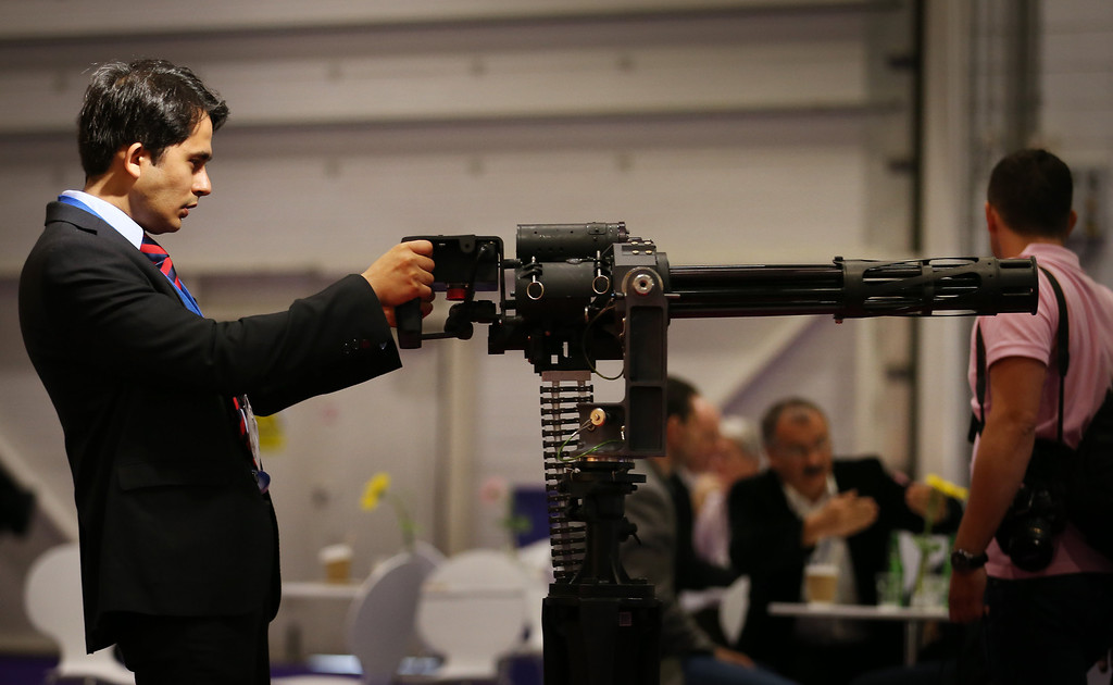 . A visitor to the Defense and Security Exhibition looks at a gun on September 10, 2013 in London, England. ExCeL London is hosting the exhibition with hundreds of manufacturers from all over the world displaying their hardware.  (Photo by Peter Macdiarmid/Getty Images)