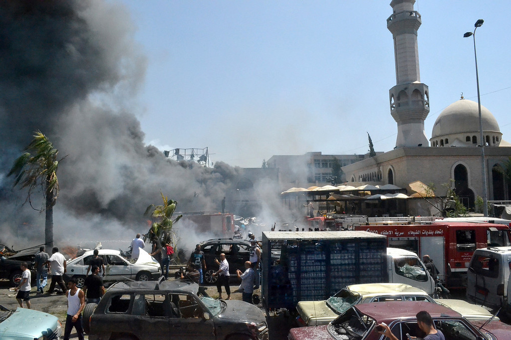 . Lebanese citizens walk between damaged cars outside a mosque after an explosion in the northern city of Tripoli, Lebanon, Friday Aug. 23, 2013.  (AP Photo)