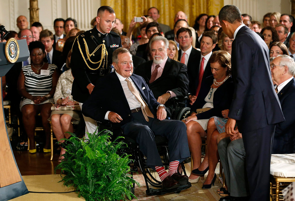 . U.S. President Barack Obama (R) stands as former President George H. W. Bush is wheeled to his seat for an event to honor the winner of the 5,000th Daily Point of Light Award at the White House in Washington July 15, 2013.   REUTERS/Kevin Lamarque