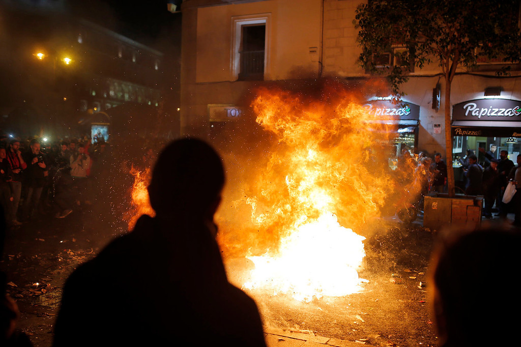 . Protestors burn trash during a demonstration against layoffs of street cleaners and garbage collectors in Madrid, Spain, Monday, Nov. 4, 2013. Trash collectors in Madrid have started bonfires and set off firecrackers during a noisy protest in one of the Spanish capitalís main squares as they prepare to start an open-ended strike. Hundreds of street cleaners and garbage collectors who work in the cityís public parks converged on the Puerta del Sol plaza late Monday. (AP Photo/Andres Kudacki)