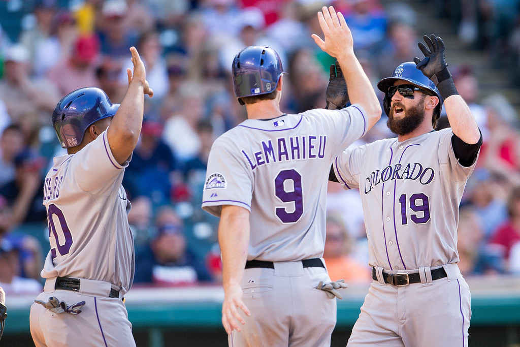 . CLEVELAND, OH - MAY 31: Wilin Rosario #20 and Vinny Castilla #9 celebrate with Charlie Blackmon #19 of the Colorado Rockies after all scored on a home run by Blackmon during the seventh inning against the Cleveland Indians at Progressive Field on May 31, 2014 in Cleveland, Ohio. (Photo by Jason Miller/Getty Images)