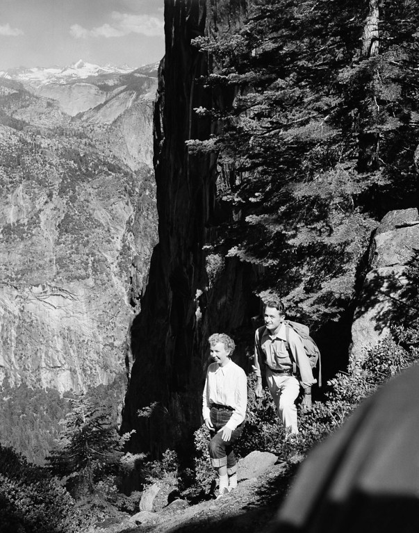. High above the floor of Yosemite Valley on the ledge climb to Glacier Point, in Yosemite National Park in California, July 8, 1952 are Robin Yelland, left, of Berkeley, Calif., and Reed Campbell, of Taft, Calif. The sheer rock wall behind them is a vertical quarter-of-a-mile. Climbers are permitted to travel upwards only because of the steepness of the trail. In distant background can be seen the high Sierra. (AP Photo/Ernest Bennett)