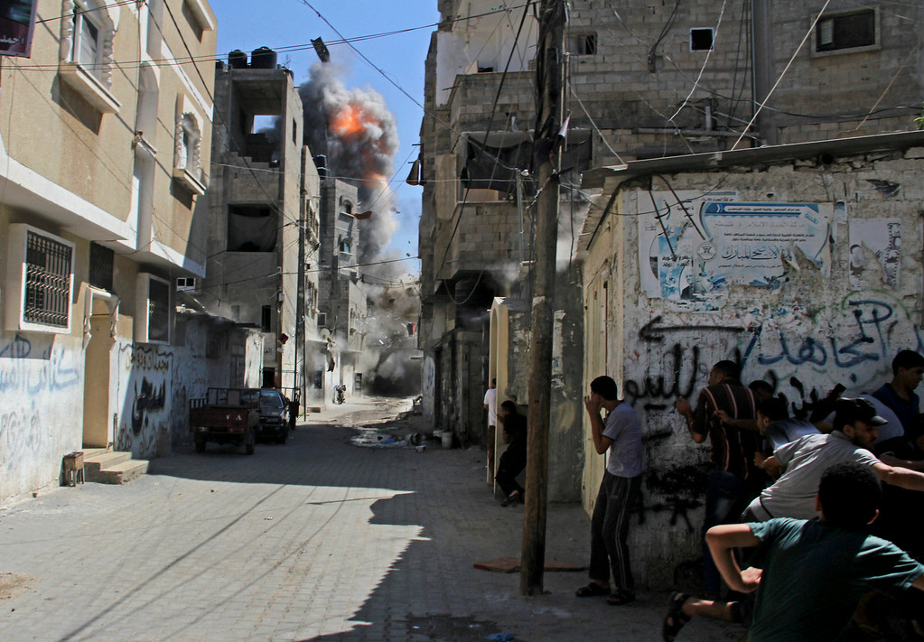 . Palestinians take cover as an Israeli strike on a building causes a ball of fire and smoke to rise in the Rafah refugee camp, southern Gaza Strip, Saturday, Aug. 23, 2014. (AP Photo/Hatem Ali)