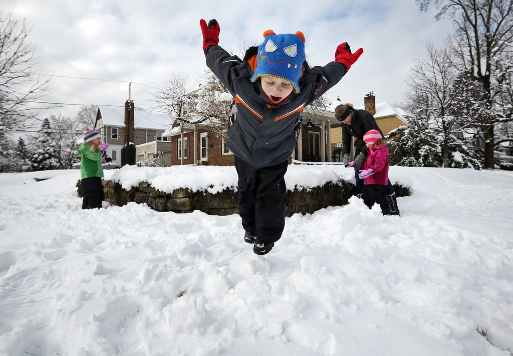 . Johnny Connell, 5, takes a dive into the snow while his twin sisters Christine and Sammy, 3, and mother Megan Connell play in the yard across from their home in Clintonville, Ohio on Wednesday, March 6, 2013.  A  late-winter storm dumped a half-foot or more of snow across much of Ohio.  (AP Photo/The Columbus Dispatch, Adam Cairns)