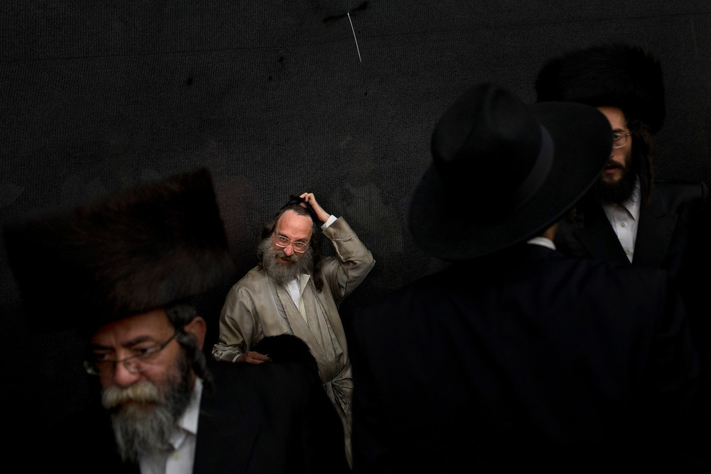 """. Ultra-Orthodox Jewish men gather during Sukkot celebrations in Jerusalem\'s Mea Shearim neighborhood, Sunday, Sept. 22, 2013. According to the Bible, during the Sukkot holiday, known as the Feast of the Tabernacles, Jews are commanded to bind together a palm frond, or \""""lulav,\"""" with two other branches, along with an \""""etrog,\""""  which makes up the \""""four species\"""" used in holiday rituals. The weeklong holiday begins on Wednesday. (AP Photo/Bernat Armangue)"""