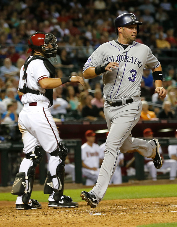 . Colorado Rockies\' Michael Cuddyer (3) scores on an Arizona Diamondbacks\' throwing error during the fourth inning of a baseball game as Diamondbacks catcher Wil Nieves looks away, Thursday, April 25, 2013, in Phoenix. (AP Photo/Matt York)