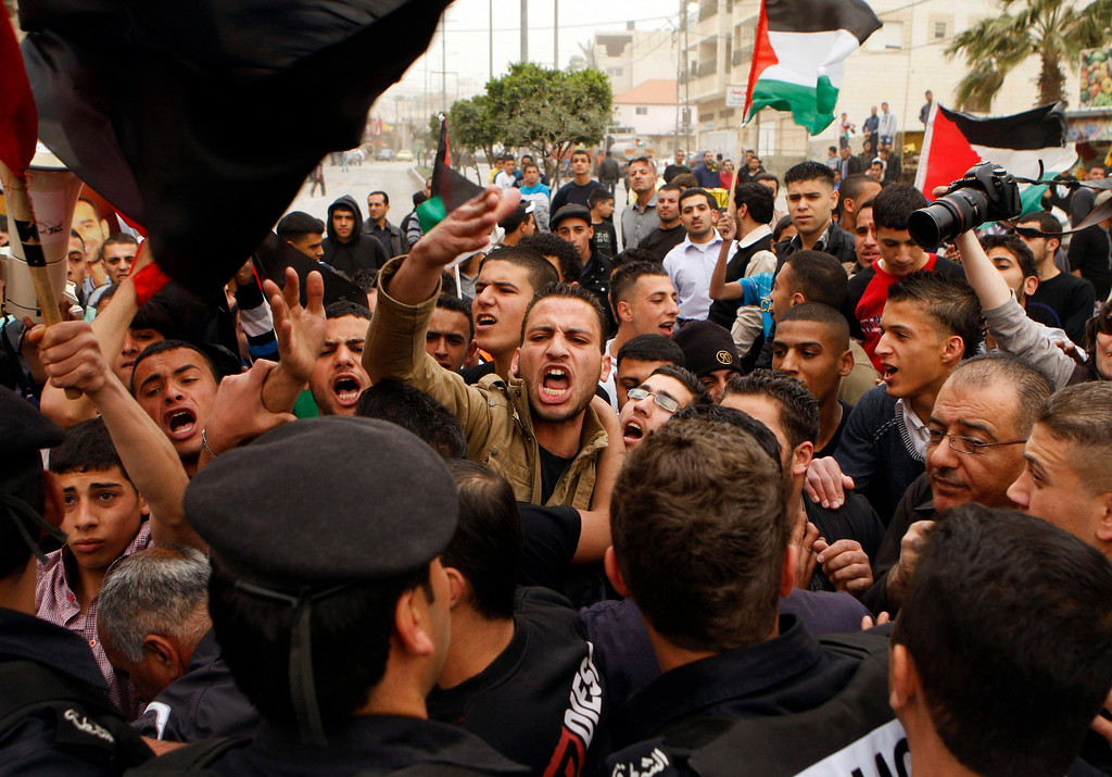 . A Palestinian protester shouts at a policeman during a demonstration against U.S. President Barack Obama\'s visit to the Church of the Nativity, revered as the site of Jesus\' birth, in the West Bank town of Bethlehem March 22, 2013. REUTERS/Mussa Qawasma