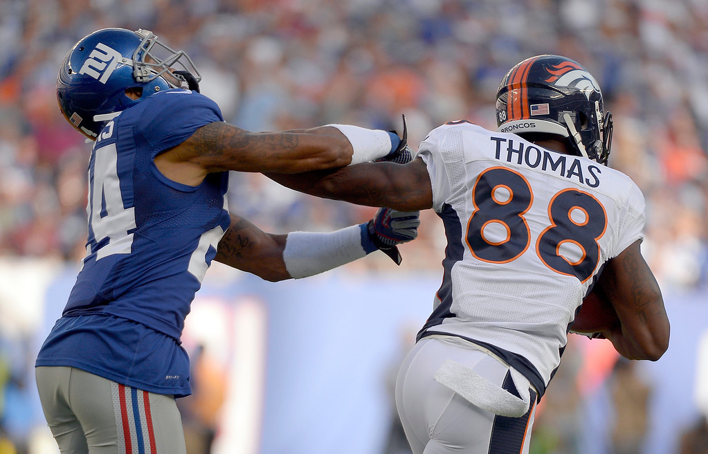 . Denver Broncos wide receiver Demaryius Thomas (88) stiff arms New York Giants defensive back Terrell Thomas (24) as he picks up a few yards during the second quarter September 15, 2013 MetLife Stadium. (Photo by John Leyba/The Denver Post)