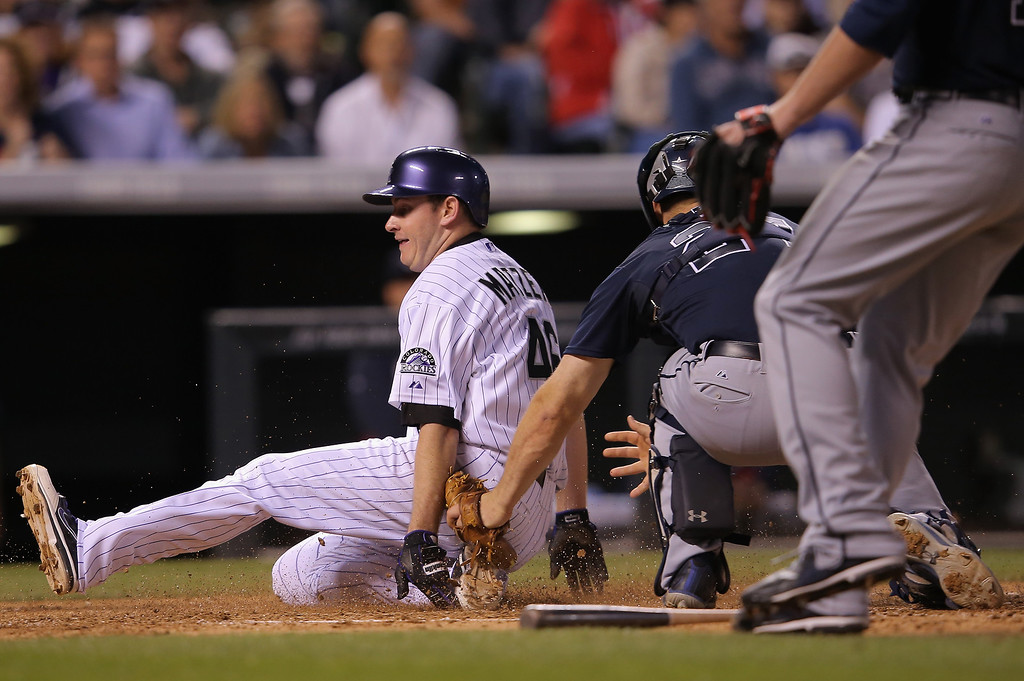 . Starting pitcher Tyler Matzek #46 of the Colorado Rockies slides home to score on a single by Troy Tulowitzki #2 of the Colorado Rockies around catcher Evan Gattis #24 of the Atlanta Braves as the Rockies take a 7-0 lead over the Atlanta Braves in the seventh inning at Coors Field on June 11, 2014 in Denver, Colorado.  (Photo by Doug Pensinger/Getty Images)