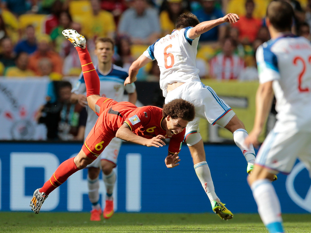 . Belgium\'s Axel Witsel, front, and Russia\'s Maksim Kanunnikov collide during the group H World Cup soccer match between Belgium and Russia at the Maracana stadium in Rio de Janeiro, Brazil, Sunday, June 22, 2014. (AP Photo/Ivan Sekretarev)