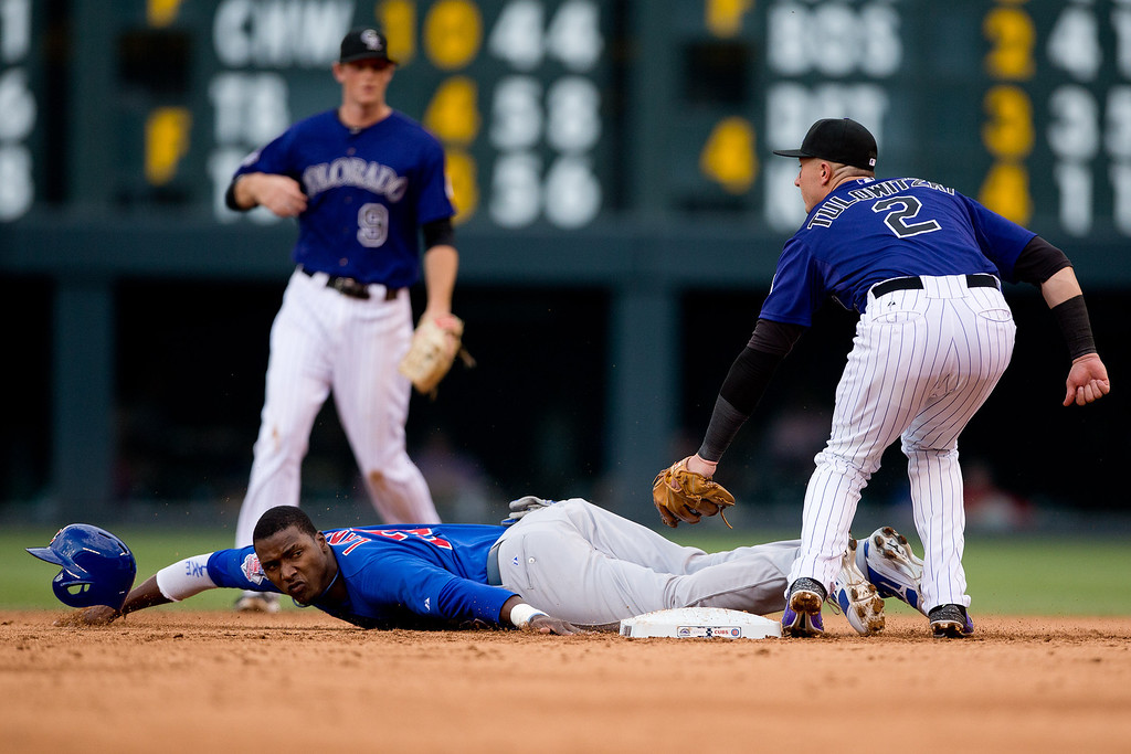 . DENVER, CO - JULY 20:  Shortstop Troy Tulowitzki #2 of the Colorado Rockies applies the tag to Junior Lake #21 of the Chicago Cubs as he is caught stealing during the second inning while second baseman DJ LeMahieu #9 looks on at Coors Field on July 20, 2013 in Denver, Colorado.  (Photo by Justin Edmonds/Getty Images)