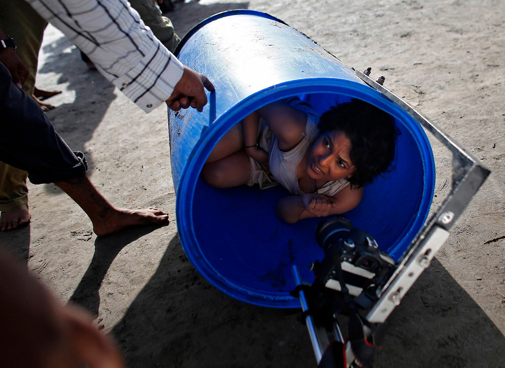". Bollywood actress Chitrashi Rawat lies in a plastic drum as she is briefed by a crew member during the shoot for the film \'Black Home\' at a beach on the outskirts of Mumbai April 26, 2013. Indian cinema marks 100 years since Dhundiraj Govind Phalke\'s black-and-white silent film ""Raja Harishchandra\"" (King Harishchandra) held audiences spellbound at its first public screening on May 3, 1913, in Mumbai. Indian cinema, with its subset of Bollywood for Hindi-language films, is now a billion-dollar industry that makes more than a thousand films a year in several languages. It is worth 112.4 billion rupees (over $2 billion) and leads the world in terms of films produced and tickets sold. Picture taken April 26, 2013. REUTERS/Danish Siddiqui"
