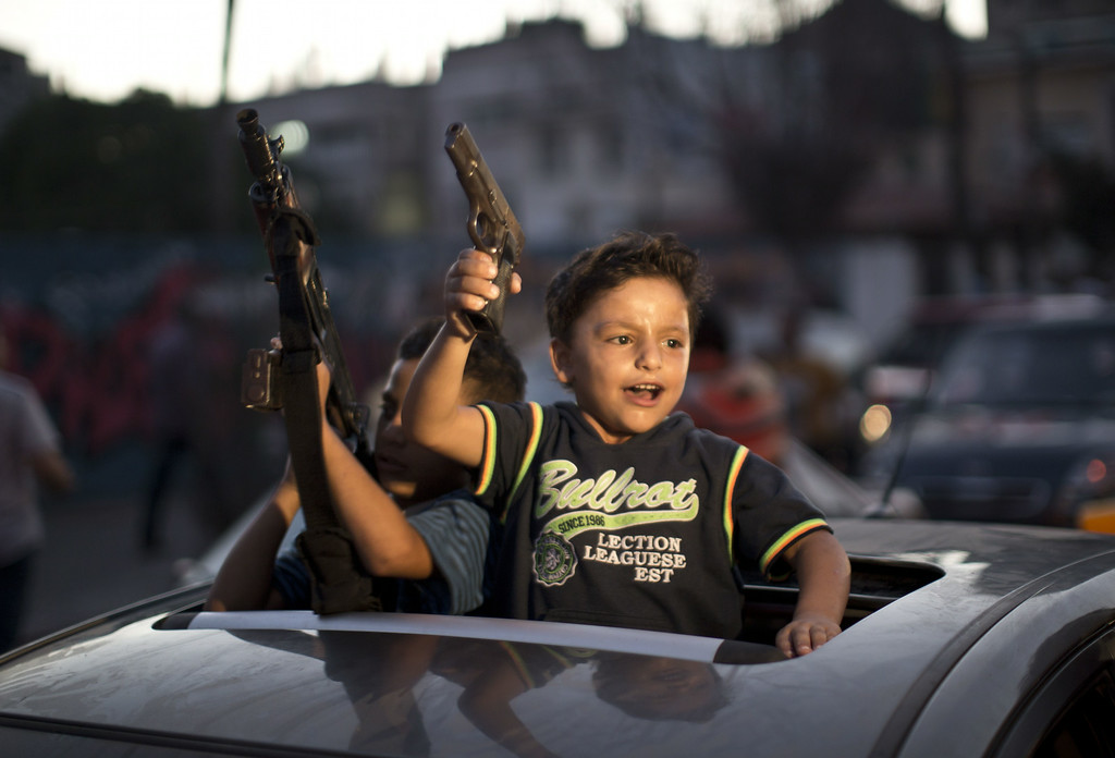 ". Children hold up guns (one with an empty magazine) from a car as Palestinians gather in the streets to celebrate after a deal had been reached between Hamas and Israel over a long-term end to seven weeks of fighting in the Gaza Strip on August 26, 2014 in Gaza City. Israel has agreed to observe an ""unlimited\"" ceasefire in the Gaza Strip, a senior official told AFP on Tuesday, shortly after the deal was announced by the Palestinians. MAHMUD HAMS/AFP/Getty Images"