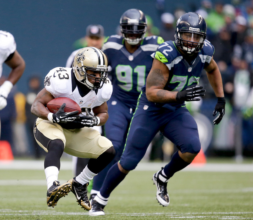 . New Orleans Saints running back Darren Sproles, left, runs past Seattle Seahawks defensive end Michael Bennett during the first quarter of an NFC divisional playoff NFL football game in Seattle, Saturday, Jan. 11, 2014. (AP Photo/Elaine Thompson)