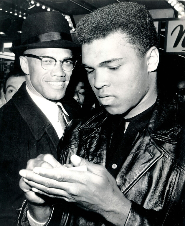 . NEW YORK, March 1, 1964 --Cassius Clay, the new world heavyweight boxing champion, signs autograph outside a downtown New York newsreel theater today as Black Muslim leader Malcolm X stands alongside.  They had just watched a screening of film on Clay\'s title fight with Sonny Liston at Miami Beach, Fla.,   Credit: AP