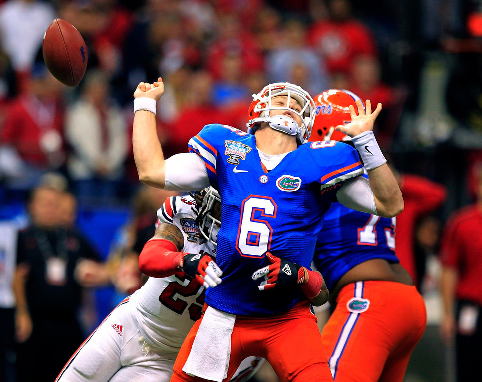 . Florida Gators quarterback Jeff Driskel loses the ball as he is sacked in the third quarter by Louisville Cardinals safety Calvin Pryor (L) during the 2013 Allstate Sugar Bowl NCAA football game in New Orleans, Louisiana January 2, 2013.  REUTERS/Sean Gardner