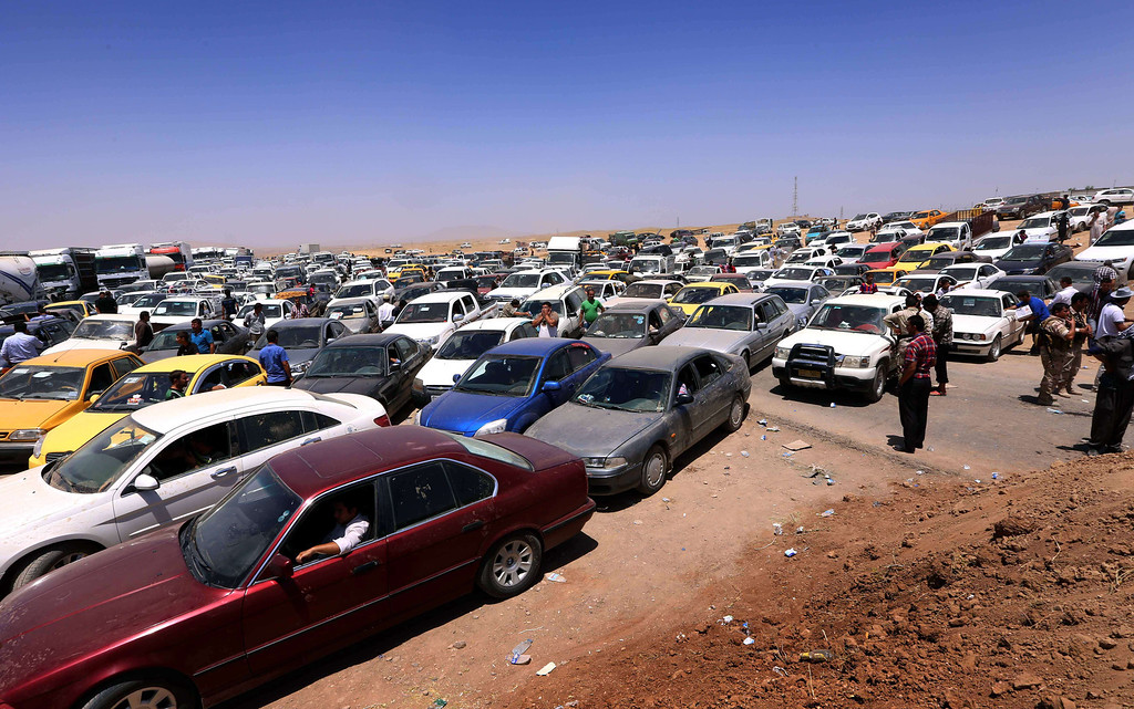 . Iraqis fleeing violence in the Nineveh province wait in their vehicles at a Kurdish checkpoint in Aski kalak, 40 kms West of Arbil, the capital of the autonomous Kurdish region of northern Iraq, on June 10, 2014. Suspected jihadists seized Iraq\'s entire northern province of Nineveh and its capital Mosul, the country\'s second-largest city, in a major blow to authorities, who appear incapable of stopping militant advances. SAFIN HAMED/AFP/Getty Images